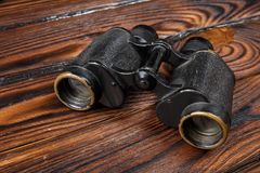 Close-up binoculars on a brown wooden table background royalty free stock image