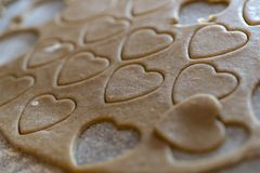 Biscuit dough with cutted out cookies in heart shape for valentines day. Close up of biscuit dough with cutted out cookies in heart shape for valentines day stock photos