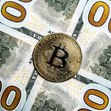A close-up of bitcoin, around which large parts of dollars. Four zeros in the corners and a coin of crypto currency with scratches. Four zeros in the corners and royalty free stock photo