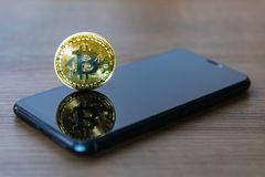 Bitcoin coin with a smartphone screen. stock photography