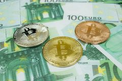 Close-up of 3 Bitcoin coins on 100 Euro banknotes. Crypto currency BTC stock photography
