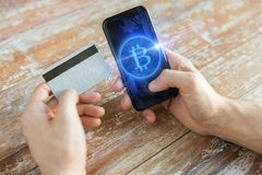 Close up of bitcoin on smartphone and credit card. Business, technology and cryptocurrency concept - close up of male hand holding smartphone with bitcoin on Stock Images
