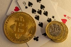 Close up of Bitcoins laying down on poker table with bunch of coins and cards in the background. Online gambling concepts royalty free stock photos