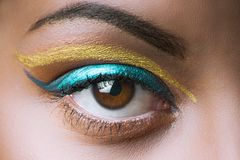 Close up of black African woman eye with golden and blue makeup Royalty Free Stock Images