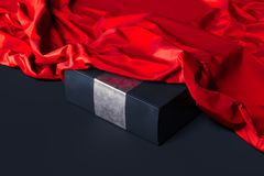 Close up of black blank box under red cloth on black background. 3d rendering. royalty free stock image