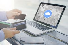 Close-up of black blank credit card and wallet in hand of businessman. On table is laptop with virtual icons of cloud. People, digital gadgets. Online Stock Images
