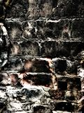 Close up of a black brick wall. Showing discolouration and decay Stock Photo
