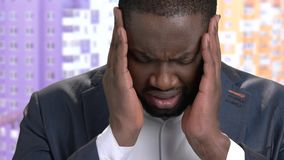 Close up black businessman suffering from headache. Face of stressed overworked dark-skinned executive having strong headache. Stress and migraine stock footage
