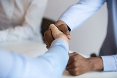 Close up black and caucasian businessmen shaking hands royalty free stock photos