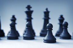 Close-up of black chess king and queen with pawns Stock Photo