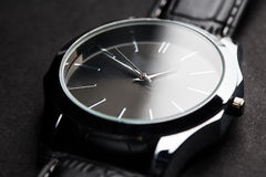 Close up of black classic male wristwatch. Time, punctuality, object and accessory concept - close up of black classic male wristwatch Royalty Free Stock Image