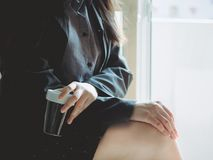 Close up black coffee cup in asian business woman hand 30s to 4. 0s hold with black shirt and skirt from coffee break time with soft focus background Stock Images