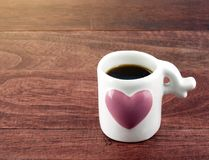 Close-up black coffee in small white coffee cup with big pink heart on dark brown wooden table floor with morning sunlight. Romantic kitchenware and hot drink Stock Photos