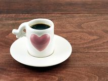 Close-up black coffee in small white coffee cup with big pink heart on white saucer and dark brown wooden table floor. Romantic kitchenware and hot drink for Royalty Free Stock Photography
