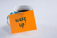 Black coffee with wake up message on white background. Close-up of black coffee with wake up message on white background stock photo
