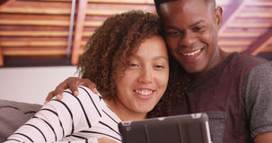 Close-up of black couple lounging on their living room couch watching videos on their tablet Stock Photography