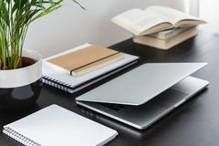 Close-up on black desk with plant, books and laptop in modern freelancer`s interior. Real photo stock photography