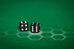Close up of black dice on green casino table Royalty Free Stock Image