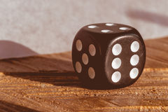 Close-up of a black dice on a wood surface, with faded and vinta Royalty Free Stock Image