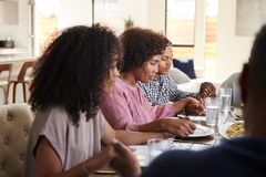 Close up of African American  family sitting at dinner table holding hands and saying grace before meal. Close up of black family sitting at dinner table holding stock images