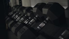 Close-up of black fitness dumbbells. New dumbbells for fitness training with weighting in fitness center. Concept of. Training equipment stock footage