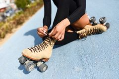 Unrecognizable black girl sitting on bike line and puts on skate. Close-up of black girl sitting on bike line and puts on skates. Unrecognizable woman Stock Photos