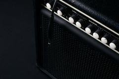 Close up of Black guitar amplifier with jack cable. On black background Royalty Free Stock Photo