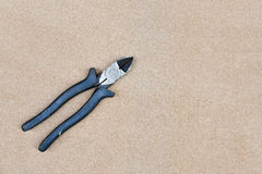 Close up of black handled wire cutter on wood background Royalty Free Stock Image