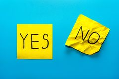 Close up black handwritten inscription yes and no word on two yellow square stickers on blue background with copy spase,. Reminder, combination of colour, choice royalty free stock photography
