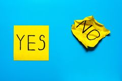 Close up black handwritten inscription yes and no word on two yellow square stickers on blue background with copy spase,. Reminder, combination of colour, choice stock image