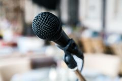 Close-up black iron microphone stands on the stage. Live music concert in a restaurant or bar in the evening. Medical staff conference concept royalty free stock photo