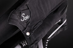 Close up of black jeans with sign Sale  hanging on clothes rack   background. Friday . Royalty Free Stock Image