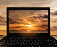 Close-up Black Laptop with landscape sunset at tropical ocean island on screen Stock Photo
