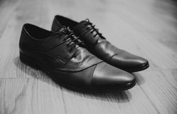 Close up on black leather boots on wood, black and white, retro Royalty Free Stock Photo