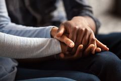 Close up black male and female holds hands. Close up black women and men in love sitting on couch two people holding hands. Symbol sign sincere feelings royalty free stock photography