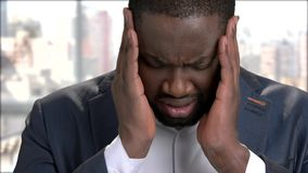Close up black man with terrible headache. Face of afro-american businessman suffering from strong headache stock footage