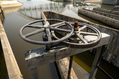 Close-up of black metal cogwheel controlling floodgate with texts in Thai language meaning `the property of` on one side. royalty free stock photo