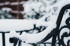 Close up of a black metal garden furniture in a garden in winter, covered in snow, snowing. Selective focus Stock Image