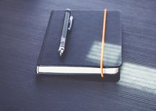 Close up black notebook with modern mechanical pencil on black w Royalty Free Stock Photography