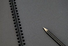 Close up at black pencil on blank black notebook,mock up for adding your content Royalty Free Stock Photography