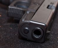 A close up of a black pistol`s muzzle. A close up of the muzzle, slide and trigger guard on a black 9mm pistol with a black background Royalty Free Stock Images