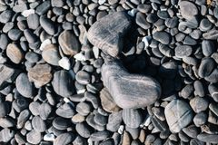 Close up of black rounded beach stones and pebble stones. royalty free stock photography