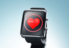 Close up of black smart watch with heart beat icon. Modern technology, object, health care and media concept - close up of black smart watch showing red heart Royalty Free Stock Photo