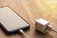 Close up of black smartphone charging battery. With cable on wooden table and sunlight with copy space and blurry background. Vintage tone and soft light Stock Photos