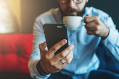 Close-up of black smartphone in man`s hand. In background, in soft focus, young bearded businessman drinks coffee. Guy uses digital gadget, checking email Royalty Free Stock Photos
