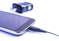 Close up black smartphone and USB cable on white background Royalty Free Stock Images