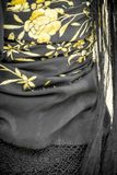 Black flamenco manton shawl with flowers. Close up of black Spanish flamenco manton shawl embroidered with yellow flowers Royalty Free Stock Photo