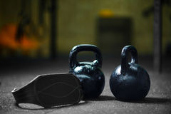 Close-up of black steel kettlebells used to perform ballistic exercises, gray athletic belt on a dark blurred background. Closeup of two steel black kettlebells stock photo