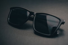 Close Up Black Sunglasses. On the Black Leather Background Stock Photos