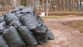 Close-up of black trash bags piled up In the city park. Close-up of black trash bags piled up In the city park stock footage
